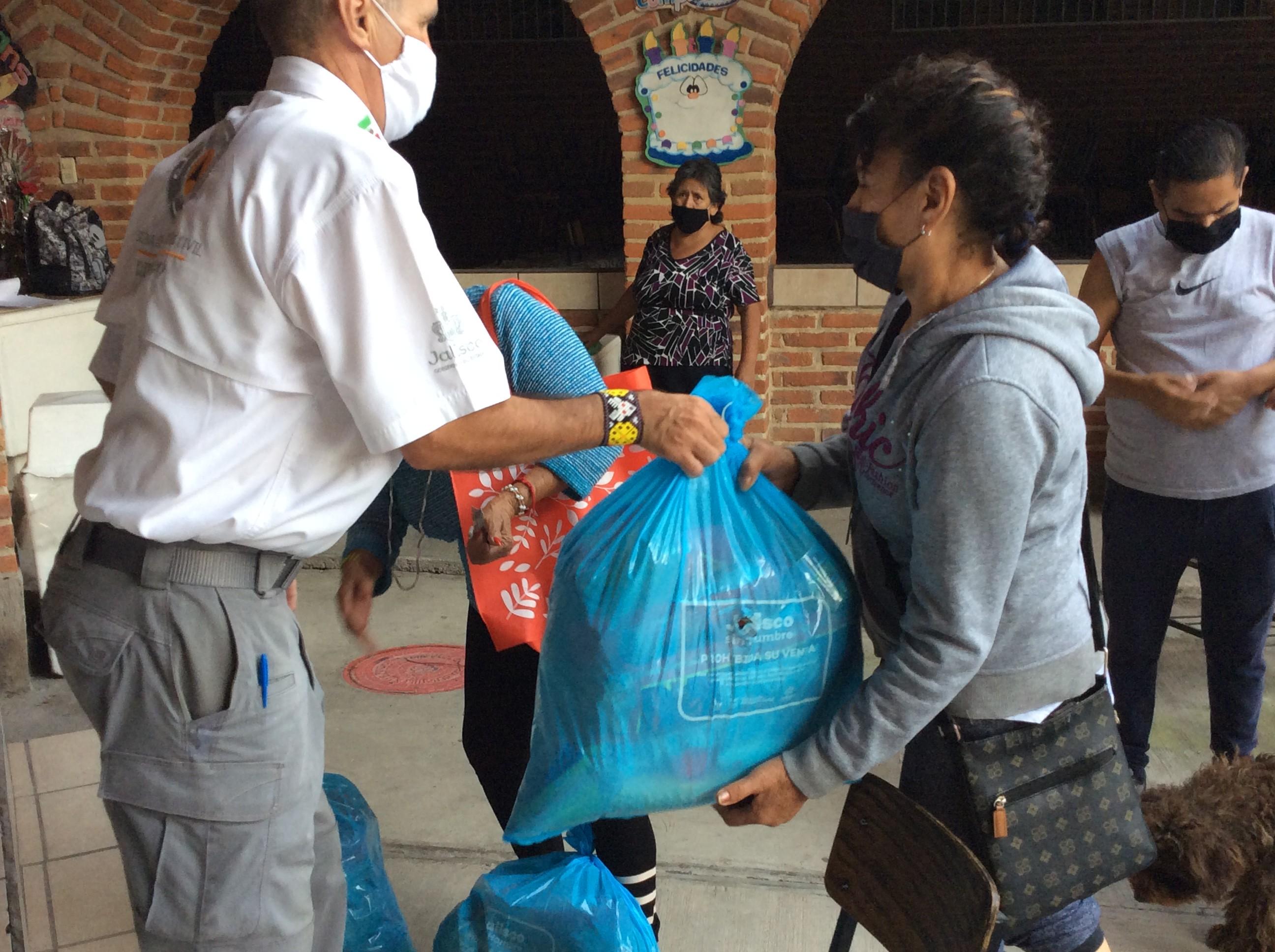 Una mujer está recibiendo su despensa de parte de personal del DIF Jalisco