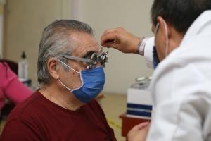 doctor revisando vista de adulto mayor